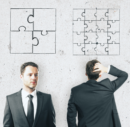 discrimination concept with two businessmen and puzzle parts on light wall