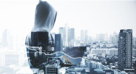 Concept de cybercriminalité avec vue arrière d'aucun pirate de visage en sweat à capuche gris avec ordinateur portable à fond de ville sombre