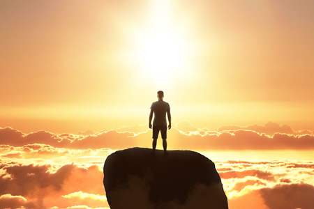 Backlit businessman on rock looking into the distance on sky background. Research and future concept 免版税图像