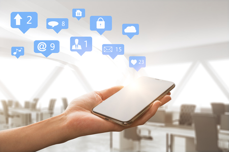 Hand holding cellphone with social media icons on blurry interior background. Communication and network concept