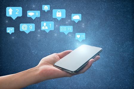Mano que sostiene el teléfono móvil con iconos de redes sociales sobre fondo de hormigón azul. Concepto de comunicación y red