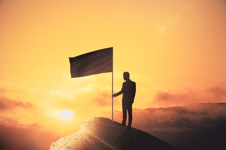 Backlit man with flag standing on cliff. Sunset background. Leadership and winner concept