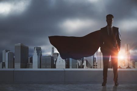 Uomo d'affari con il capo dell'eroe rosso in piedi sul tetto con lo sfondo della città. Leadership e concetto di successo