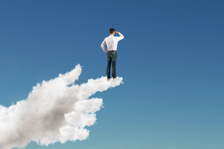 looking for decision concept with businessman standing on forefinger of cloud hand and staring into the distance at blue sky background