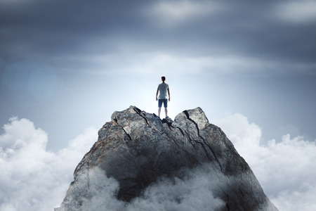 Businessman standing on abstract mountain on sky background. Promotion and leader concept