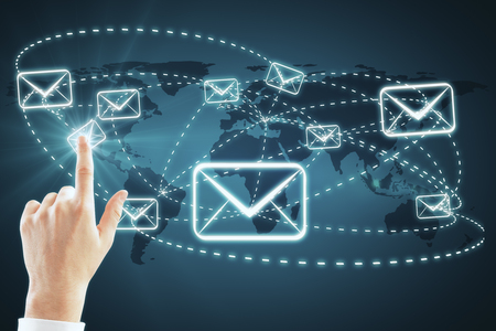 Hand with digital email icons on blue background with map. E-mail marketing and newsletter concept