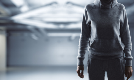 Unrecoignizable woman with hood standing in blurry interior with copy space. Hacker and data concept. 3D Rendering