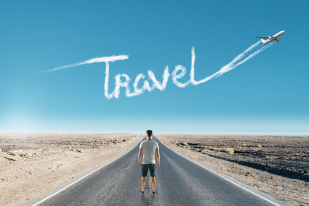Casual man on road with airplane in sky and travel text cloud. Traveling, transportation and trip concept Stock Photo