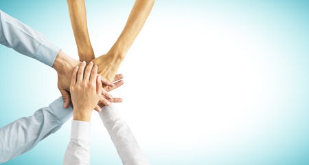 Hands put together on blue background with copy space. Union, togetherness and teamwork concept