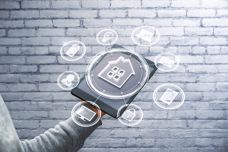 Hand holding pad with abstract smart home interface on brick wall background. Technology and future concept 写真素材