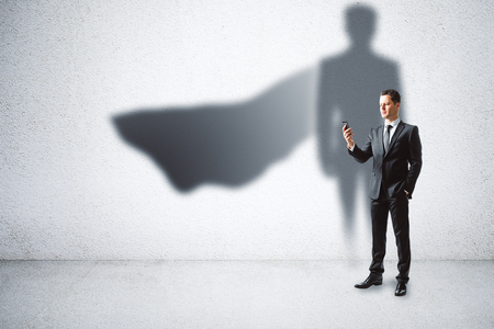 European businessman with super hero cape shadow standing on concrete wall background. Leadership and security concept