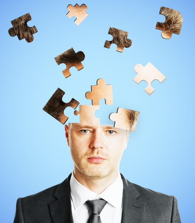 Puzzle headed businessman on light background. Confusion and challenge concept Stock Photo