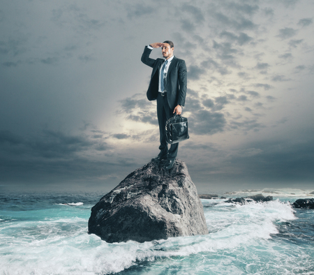Young businessman with briefcase looking into the distance while standing on rock on sky and sea background. Research and vision concept