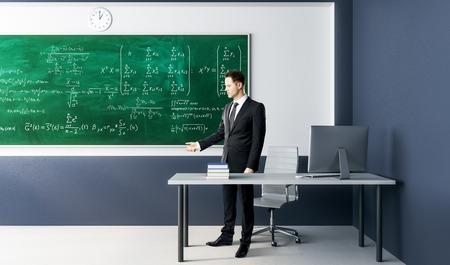 Geschäftsmann, der im modernen Klassenzimmerinnenraum mit Algebraformeln auf Tafel steht. Wissenschafts-, Bildungs- und Unterrichtskonzept.
