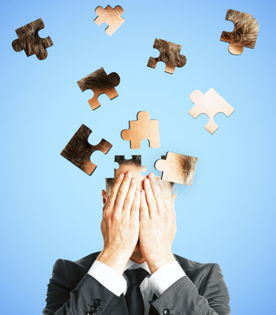 Puzzle headed businessman on light background. Confusion and jigsaw concept