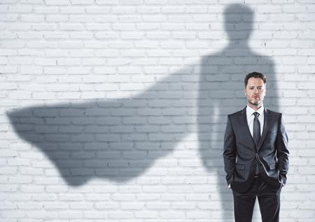 Uomo d'affari europeo con l'ombra del capo super eroe in piedi sul fondo del muro di mattoni. Leadership e concetto di successo