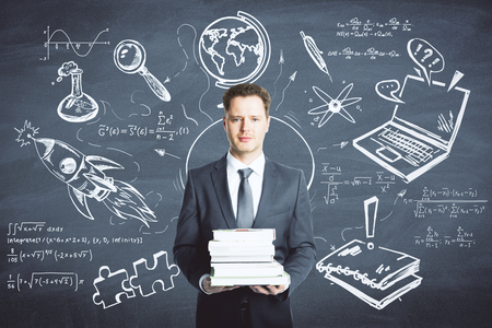 Businessman holding books on chalkboard background with business sketch. Education and finance concept