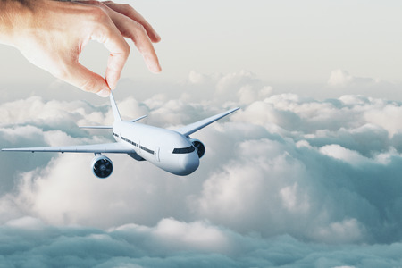 Male hand holding aircraft on blue sky background. Travel concept. 3D Rendering