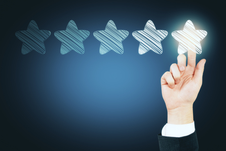 Businessman hand with glowing star rating. Feedback and performance concept 版權商用圖片