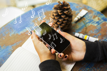 Hand holding phone with notes. Music, hobby and app concept