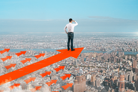 Businessman standing on abstract arrows on sky and city background. Success and leadership concept