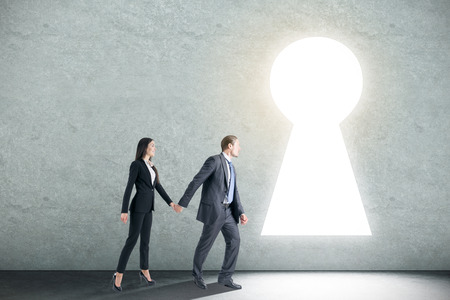 Businessman and woman holding hands in abstract concrete interior with glowing keyhole opening. Teamwork, dream and success concept. 3D Rendering