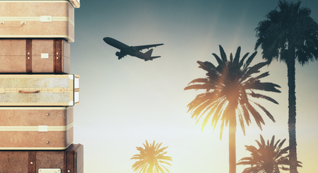 Suitcases stacked on creative vacation background with backlit palm trees and aiplane. Travel and transportation concept