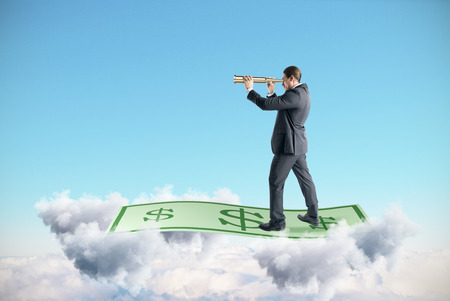 Businessman looking into the distance with binoculars while standing on dollar banknote in sky with clouds. Money and banking concept Stock Photo