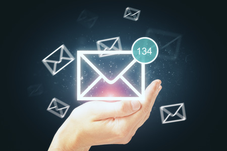 Hand holding glowing digital business email interface on dark background. Newsletter and app concept. 3D Rendering