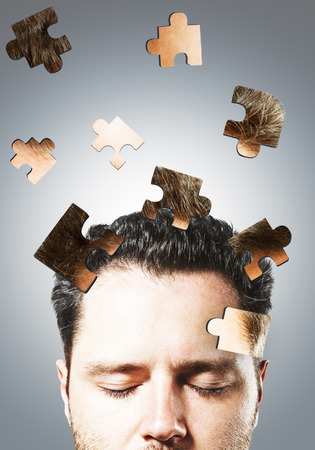 Puzzle headed businessman on gray background. Confusion and think concept