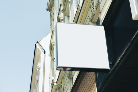 Empty square white signage on building with classical architecture and daylight. Mock up
