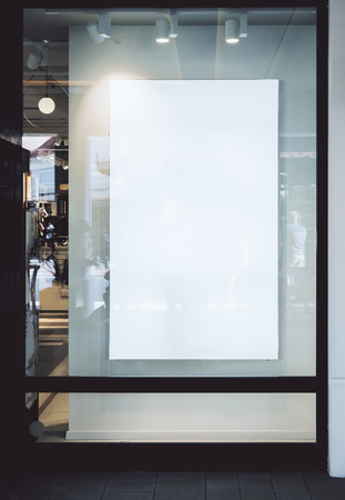 Empty white rectangular poster behind glass with reflections. Mock up Banco de Imagens