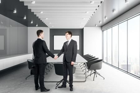Two handsome young white businessmen shaking hands in modern meeting room interior with city view and daylight. Teamwork concept. 3D Rendering Banque d'images - 107087152