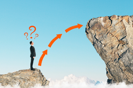 Side view of young businessman on small cliff thinking how to get onto big one. Career development and growth concept 스톡 콘텐츠