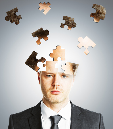 Puzzle headed businessman on light background. Confusion and maze concept