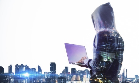 Side view of hacker with laptop computer on city background with copy space. Hacking and computing concept. Double exposure