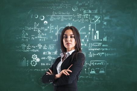 Portrait of attractive young european businesswoman with folded arms standing on chalkboard background with mathematical formulas. Education and science concept