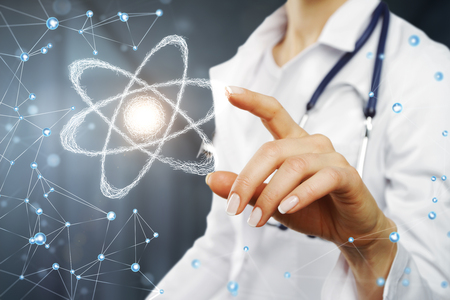 Female doctor pointing at glowing polygonal atom interface. Science and medicine concept Фото со стока