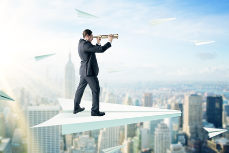 Businessman looking into the distance with binoculars while standing on abstract paper plane on blurry city background. Leadership and occupation concept