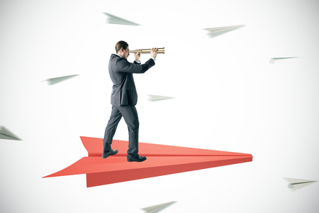 Businessman looking into the distance with binoculars while standing on abstract paper plane on white background. Leadership and forward concept Stock Photo