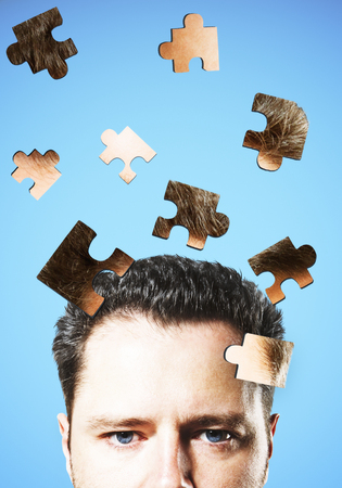 Puzzle headed businessman on blue background. Confusion and pensive concept