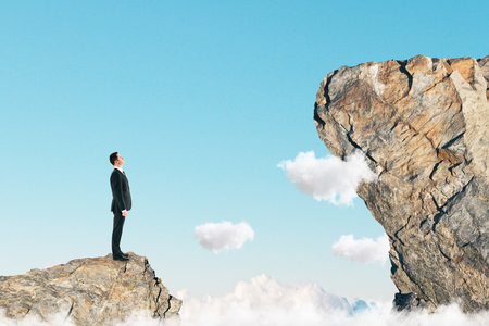 Side view of young businessman on small cliff thinking how to get onto big one. Career development and promotion concept 스톡 콘텐츠