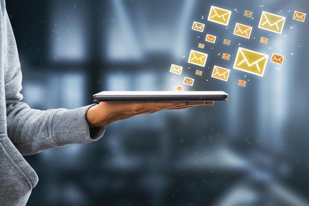 Vue latérale de la main tenant le pad avec des icônes de courrier électronique dessinés sur fond blanc. Concept de marketing par e-mail