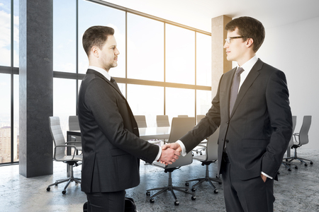 Businessmen shaking hands in concrete conference room interior with city view and daylight. Teamwork and success concept. 3D Rendering