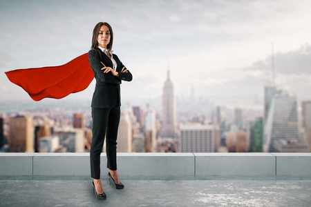 Attractive young european woman with red hero cape and folded arms standing on city background. Superhero and solution concept