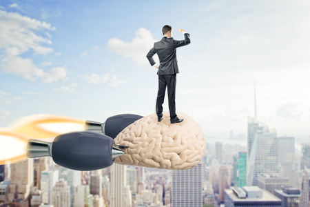 Businessman looking into the distance on abstract launching brain rocket. Sky and city background. Brainstorm and success concept. 3D Rendering 版權商用圖片