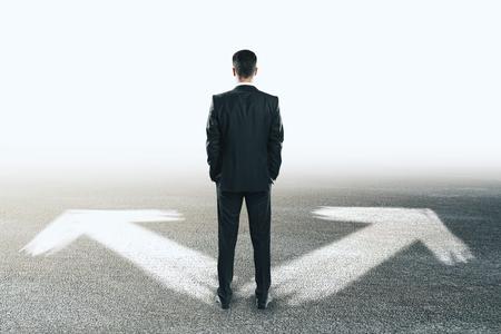 Uomo d'affari con le frecce su sfondo concreto. Direzione diversa e concetto futuro