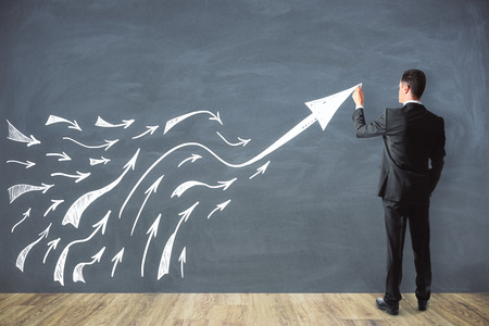 Businessman drawing arrows on chalkboard background. Future and forward concept
