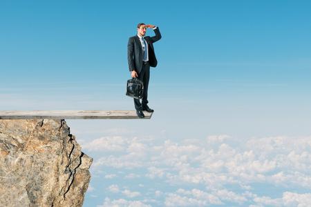 Uomo d'affari che esamina la distanza dalla cima della montagna sul fondo del cielo. Successo e concetto di ricerca