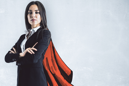 Portrait of attractive young european businesswoman with drawn cape on concrete wall background. Leadership and protection concept Stockfoto